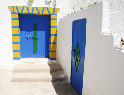 Painted doors of white houses in Tafadna