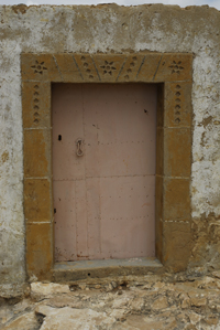 A pink painted door with rektangular portal with  sexleaves roses
